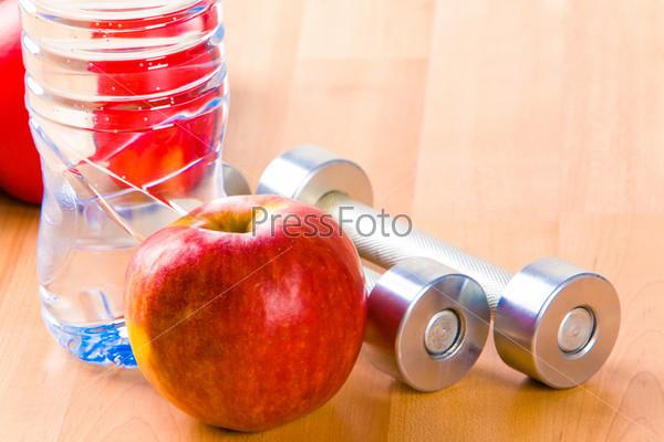 Красное яблоко, гантели и минеральная вода