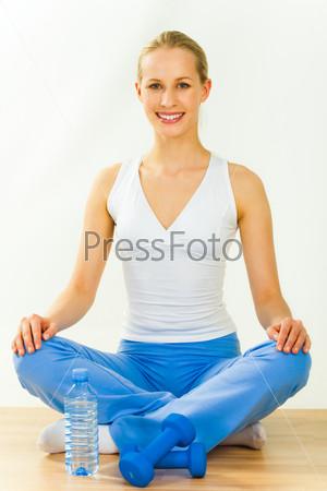 Девушка сидит в позе лотоса на полу