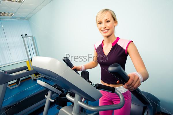 Девушка на тренажере в спортивном зале