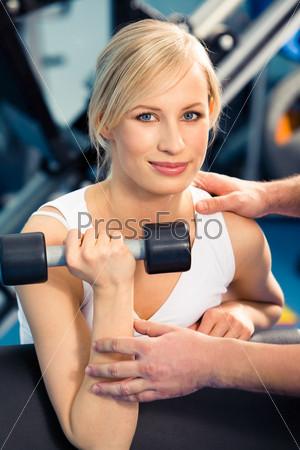 Девушка занимется в тренажерном зале под наблюдением инструктора