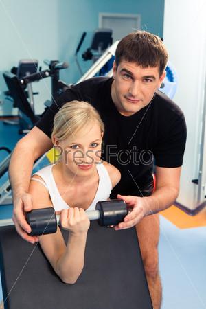 Девушка с инструктором выполняет упражнение