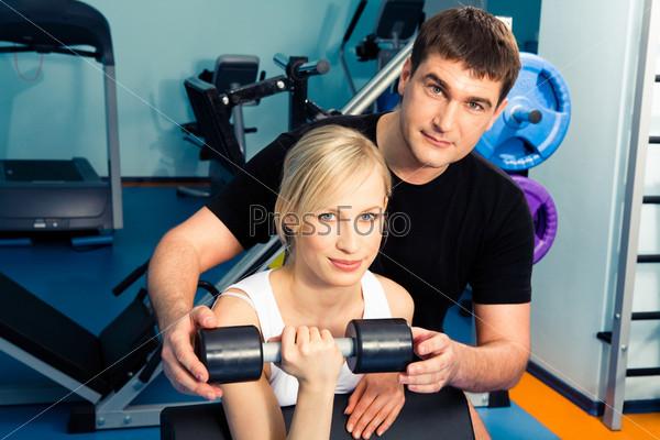 Фотография на тему Блондинка с инструктором выполняют комплекс упражнений в зале