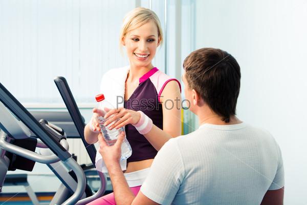 Парень подает девушке в тренажерном зале бутылку с водой