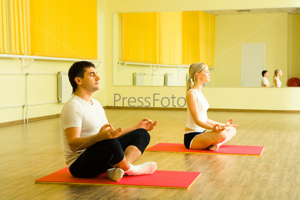 Мужчина и женщина медитируют на занятиях йогой