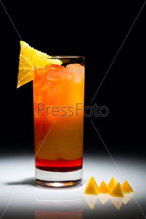Коктейль кампари оранж с кусочками фруктов лежащих рядом с бокалом