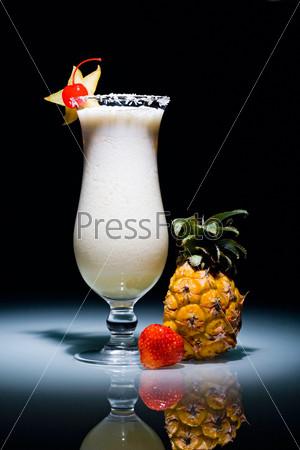 Знаменитый коктейль пина-колада с вишенкой, рядом лежат клубника и ананас
