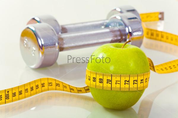 Зеленое яблоко, обмотанное сантиметром, на фоне металлических гантелей