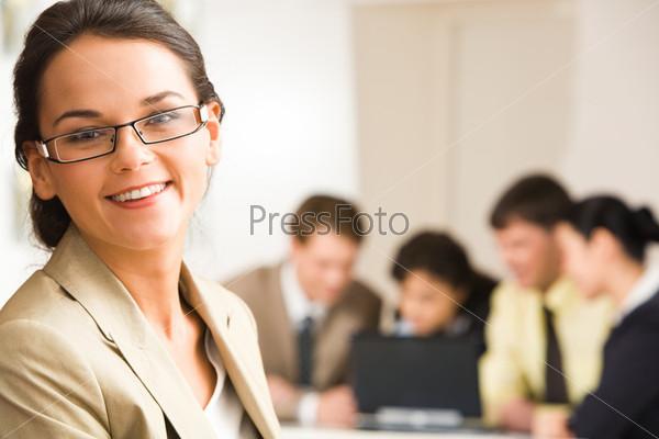 Стильная брюнетка улыбается на фоне коллег на заднем плане