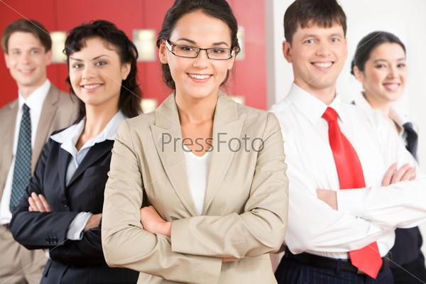 Команда успешных менеджеров стоит глядя в камеру с улыбками