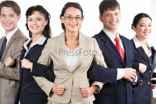 Команда сотрудников стоит близко друг к другу символизируя сплоченность