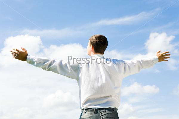 Парень в белой рубашке стоит спиной на фоне неба