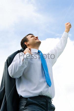 Деловой мужчина подняв руку стоит на фоне голубого неба