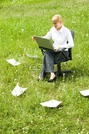 Девушка сидящая на поляне с ноутбуком в окружении разбросанных бумаг
