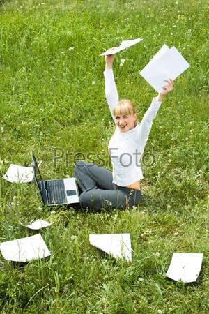 Деловая женщина сидит на природе с документами подняв руки вверх