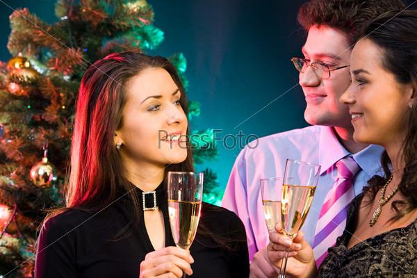 Молодые люди общаются во время рождественской вечеринки