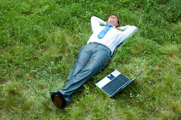 Бизнесмен лежит на траве рядом с ноутбуком и мечтает