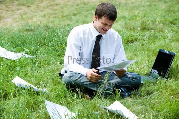 Фотография на тему Деловой бизнесмен в окружении бумаг сидит на траве