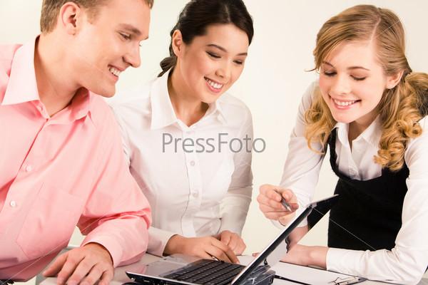 Коллеги по работе обсуждают документы склонившись за столом
