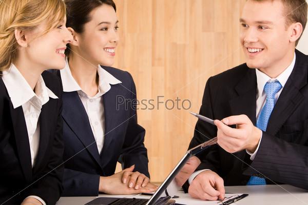 Офисные сотрудники сидят за столом и улыбаются