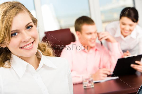 Крупный план девушки в офие на фоне коллег