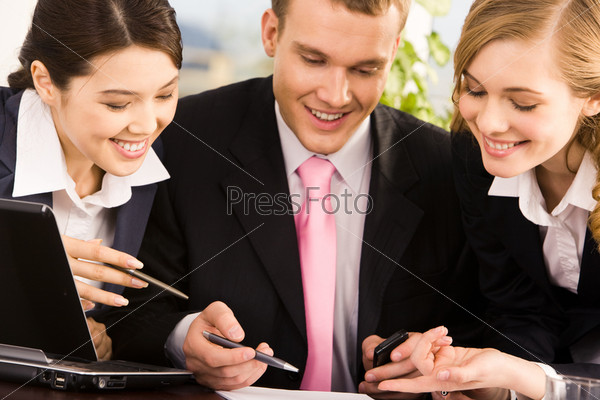 Успешный бизнесмен за столом в окружении двух девушек