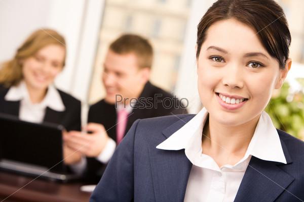 Деловая женщина смотрит в камеру с улыбкой на фоне своих коллег