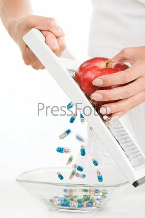 Девушка трет красное яблоко на терке, а в миску сыпятся пилюли