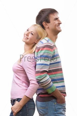 Счастливая пара стоит спинами друг ко другу и смеется
