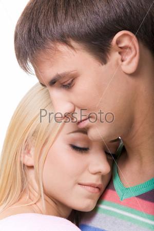 Девушка и парень стоят близко друг ко другу и на их лицах изображены любовь и тепло друг ко другу