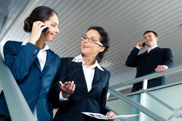 Две красивые деловые женщины спускающиеся вниз по лестнице