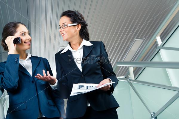 Деловые женщины идут вниз по офисному зданию и общаются между собой