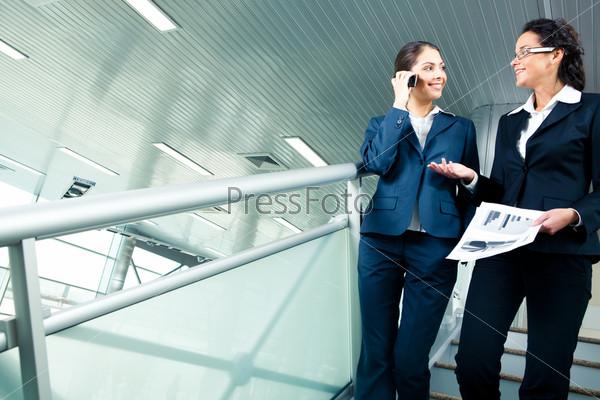 Две девушки спускаются вниз по лестнице и разговаривают