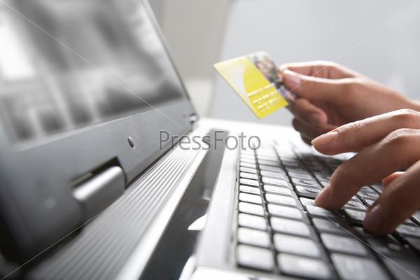 Рука держащая кредитную карту за клавиатурой компьютера