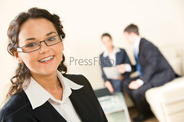 Счастливая деловая женщина крупным планом на фоне коллег