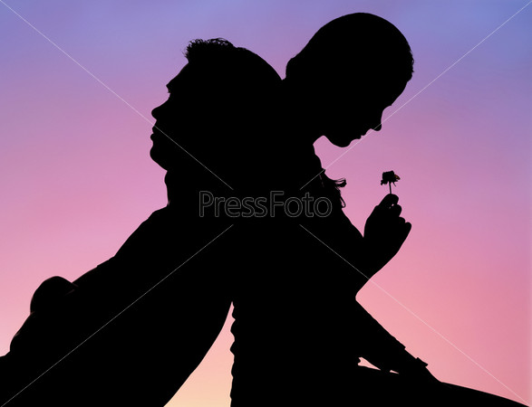 Силуэты романтичных влюбленных, сидящих спинами друг ко другу на фоне заката