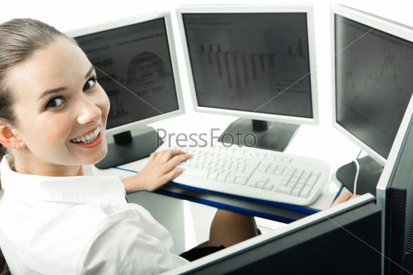 Довольная девушка в белой рубашке сидит перед мониторами