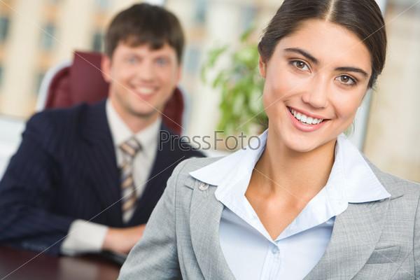 Деловая женщина улыбается в камеру на фоне довольного руководителя