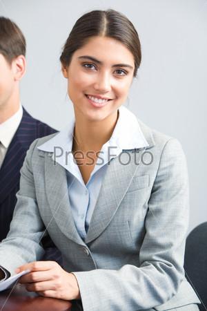 Молодая девушка в костюме сидит за столом и улыбается в камеру