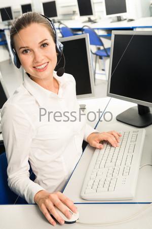 Доброжелательная девушка в наушниках за рабочим столом