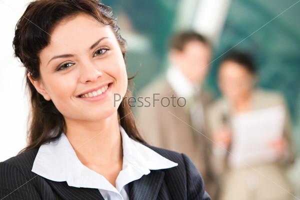 Красивая девушка в деловом костюме на фоне своих коллег в офисе