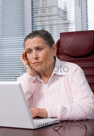 Усталая женщина в возрасте перед экраном ноутбука