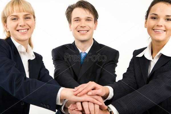 Дружная команда стоит держась за руки символизируя сплоченность