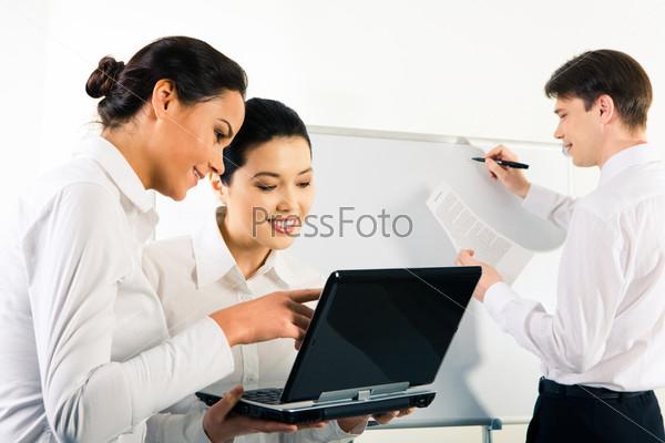 Две современные девушки смотрят в монитор на фоне молодого человека у доски
