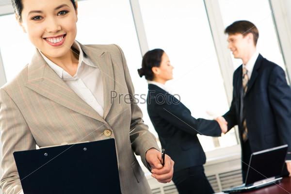 Уверенная деловая женщина смотрит в камеру с улыбкой