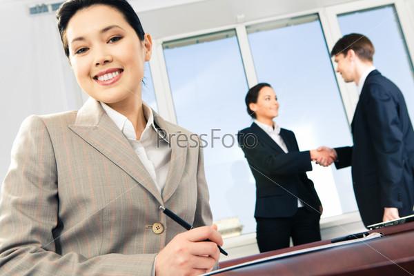 Привлекательная бизнесменша уверенно улыбается на фоне своих сотрудников