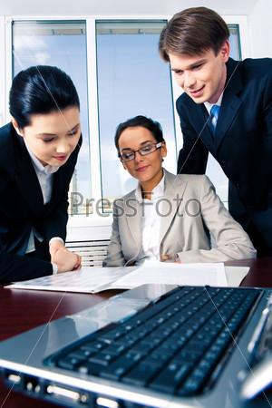 Сотрудники склонившиеся над документами за рабочим столом