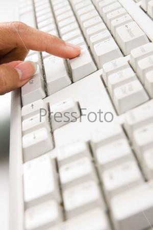 Женский палец нажимает на клавишу клавиатуры