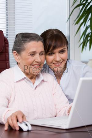 Пожилая женщина консультирует девушку по работе с ноутбуком