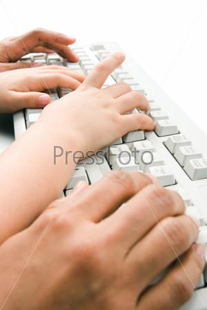 Руки девушки и ребенка на клавиатуре