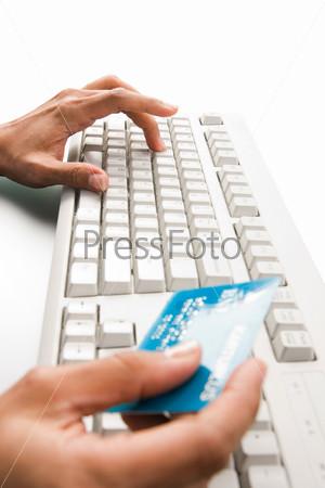 Крупный план женских рук, одна из которых нажимает клавишы на клавиатуре компьютера, в другой кредитная карточка